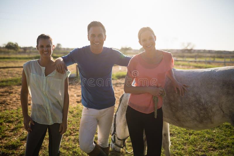 Stående av den manliga instruktören med unga kvinnor som står vid hästen royaltyfri bild