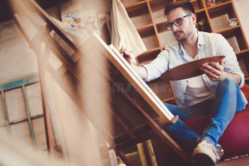 Stående av den manliga konstnären Working On Painting i studio arkivbild