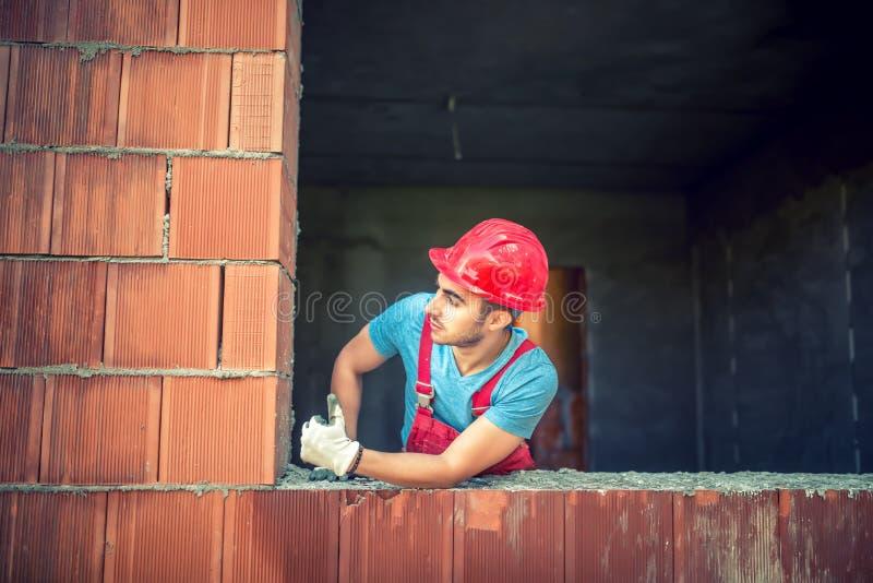 Stående av den manliga konstruktionsteknikern som godkänner på kvalitets- kontroll av det nya huset industriell lokal för konstru royaltyfri fotografi