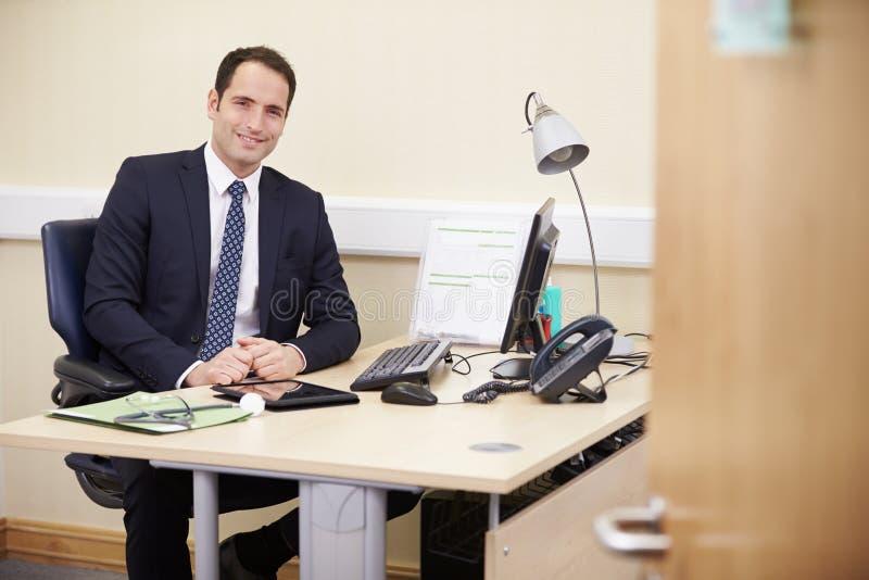 Stående av den manliga konsulenten Working At Desk i regeringsställning arkivfoton
