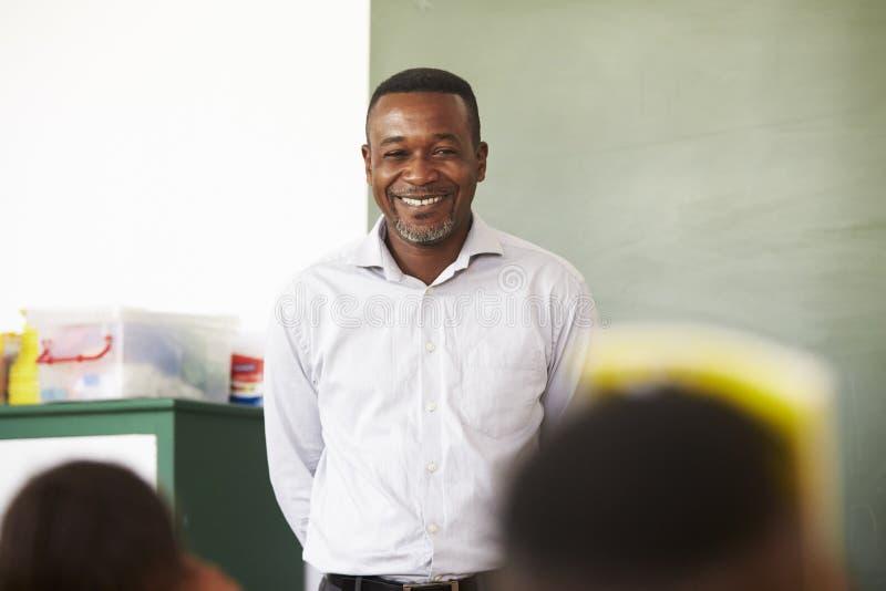 Stående av den manliga läraren på en grundskola i Afrika arkivfoton