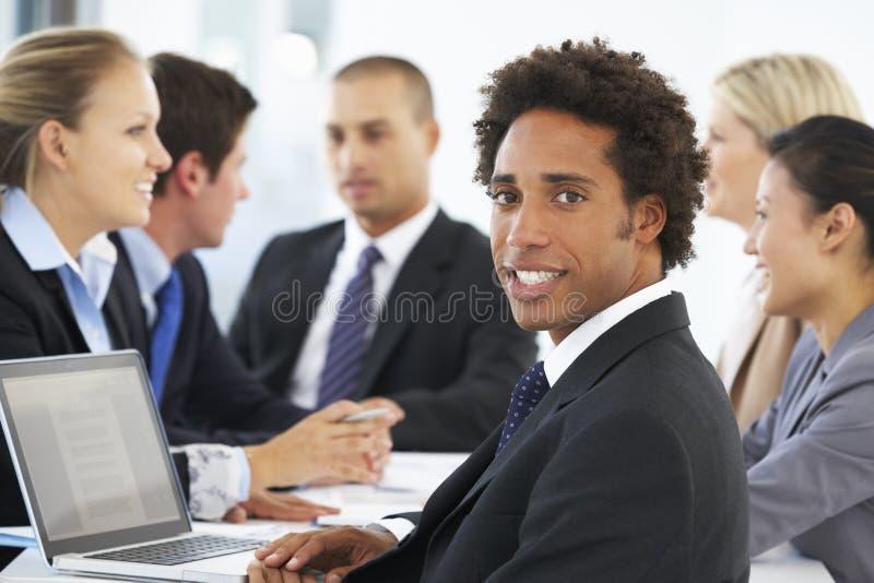 Stående av den manliga ledaren med kontorsmöte i bakgrund royaltyfria bilder