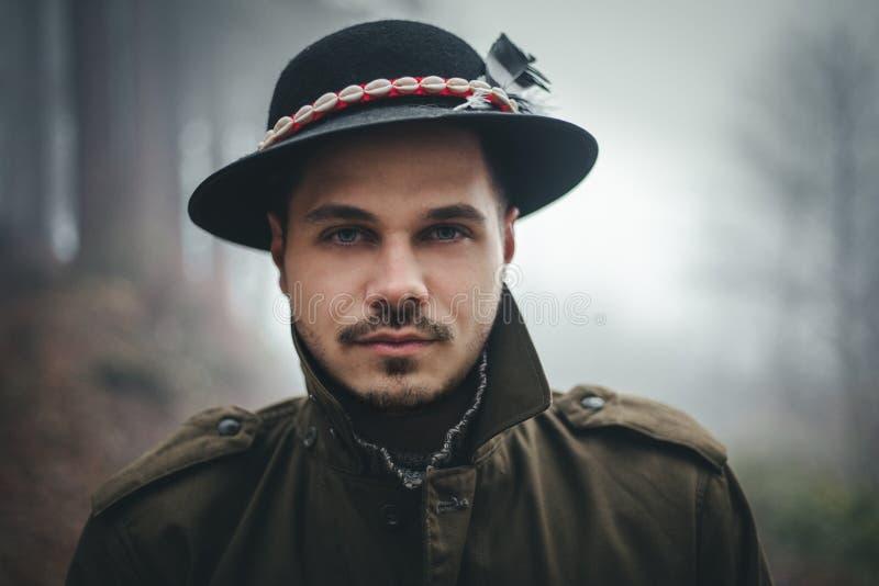 Stående av den manliga modellen med hatten och härliga ögon i djup skog på skymning Skogsarbetare i den dimmiga och dimmiga skoge royaltyfri bild
