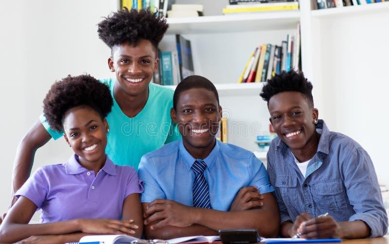 Stående av den manliga professorn med afrikansk amerikanstudenter som ser kameran royaltyfria bilder