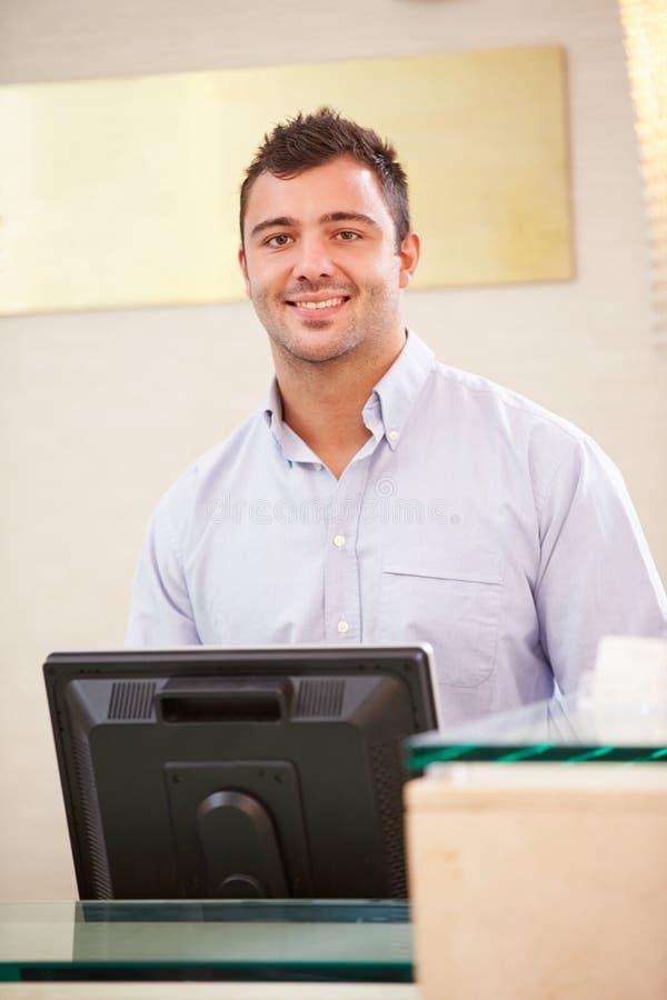 Stående av den manliga receptionisten At Hotel Front Desk royaltyfri fotografi