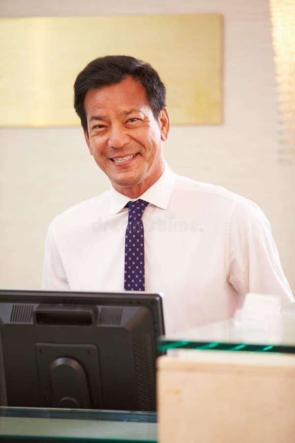 Stående av den manliga receptionisten At Hotel Front Desk arkivfoto