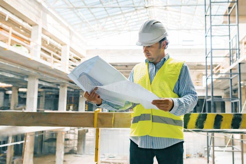 Stående av den manliga teknikern på konstruktionsplatsen Byggmästaren ser planet av konstruktionsplatsen Byggnad utveckling, team arkivfoto