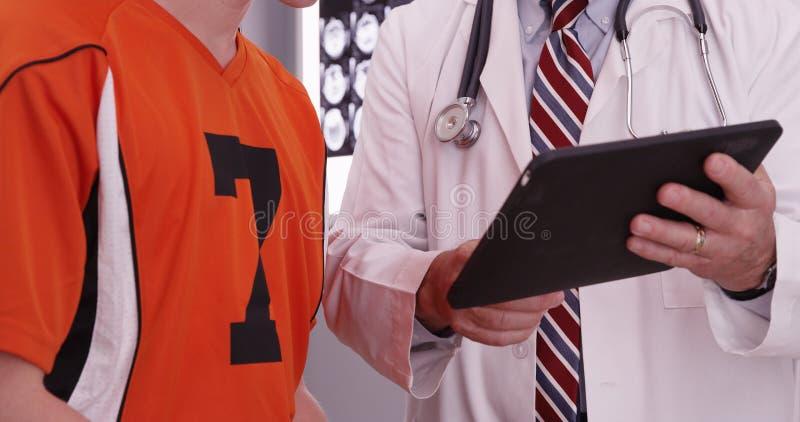 Stående av den medicinska doktorn som ser minnestavladatoren med colle royaltyfria foton