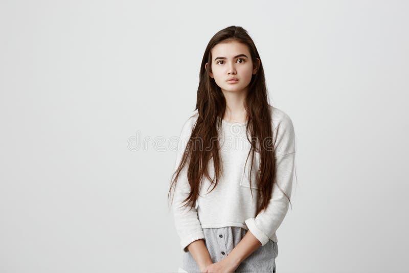 Stående av den mjuka brunettflickan för barn med långt mörkt hår och sund hud som bär lös tillfällig kläder som ser royaltyfri fotografi