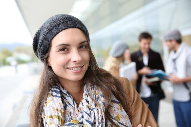 Stående av den moderiktiga studentflickan framme av universitetet arkivfoton