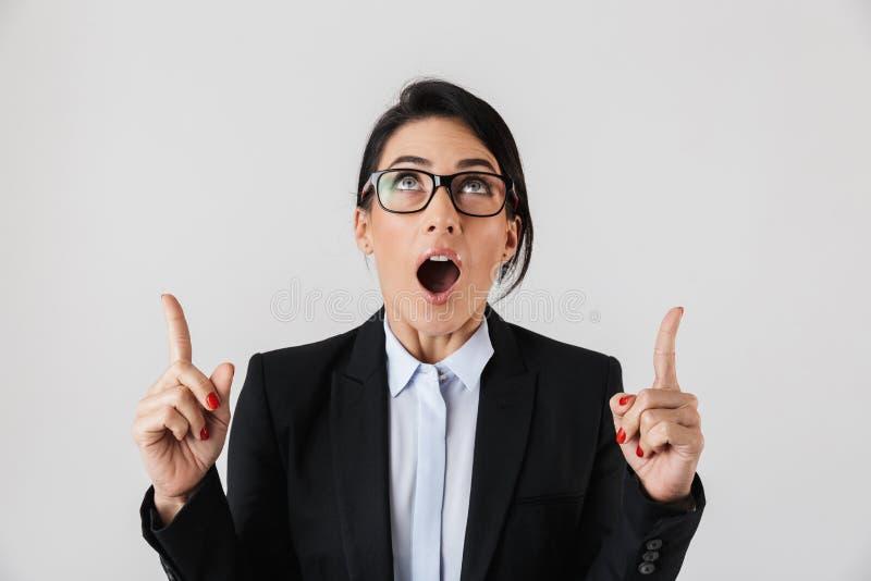 Stående av den moderna affärskvinna30-tal i formella kläder och glasögon som uppåt som pekar fingrar isoleras över vit bakgrund royaltyfri fotografi