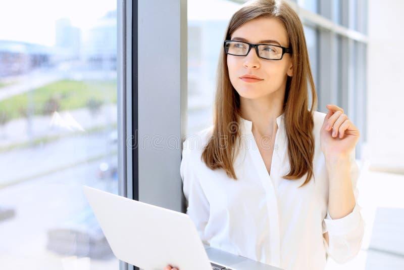 Stående av den moderna affärskvinnan som arbetar med bärbar datordatoren i kontoret, kopieringsutrymmeområde royaltyfri bild