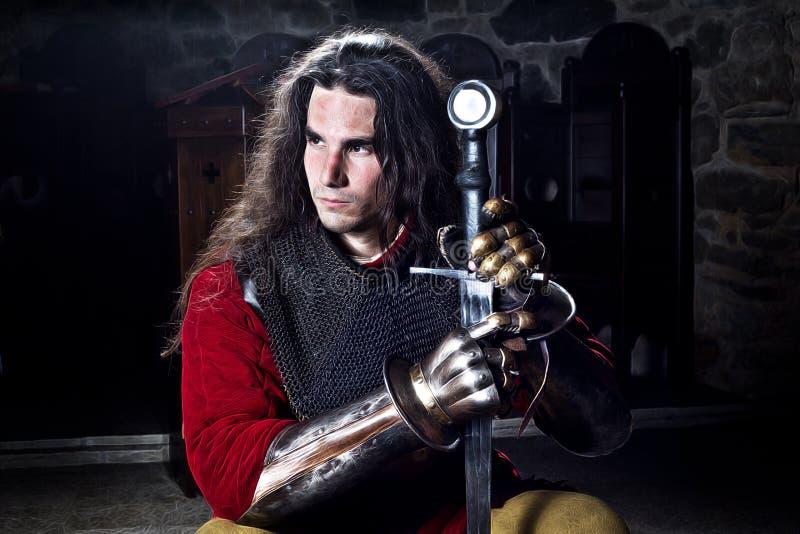 Stående av den modiga riddaren With Sword Against Stonewall royaltyfri bild