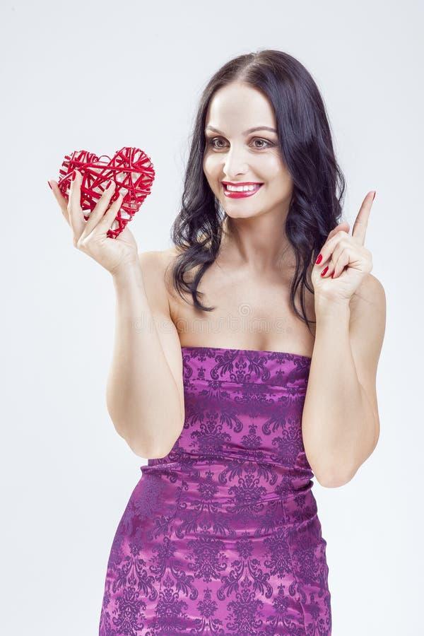 Stående av den mogna Caucasian kvinnan som poserar med röd vide- hjärta arkivfoton