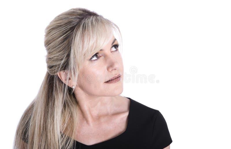 Stående av den mogna härliga blonda kvinnaframsidan som ser upp royaltyfri fotografi