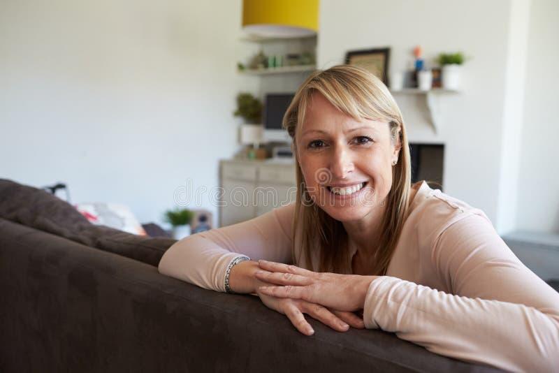 Stående av den mogna kvinnan som kopplar av på Sofa At Home arkivfoton