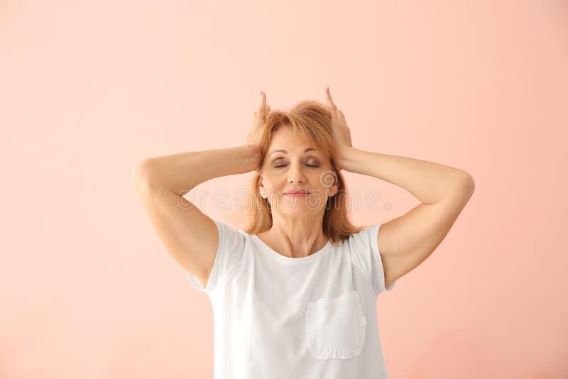 Stående av den mogna kvinnan som trycker på händer till hennes huvud på färgbakgrund fotografering för bildbyråer