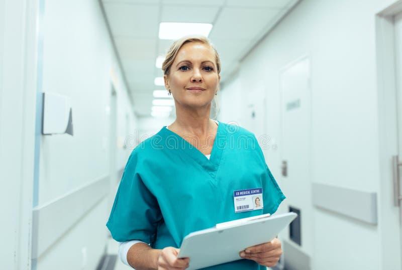Stående av den mogna kvinnliga sjuksköterskan som arbetar i sjukhus royaltyfri foto