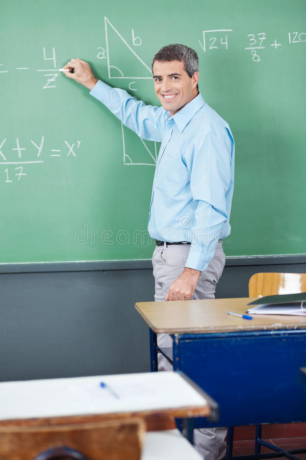Stående av den mogna läraren Writing On Board royaltyfri fotografi