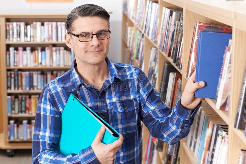 Stående AV den mogna manliga studenten Studying In Library royaltyfri foto