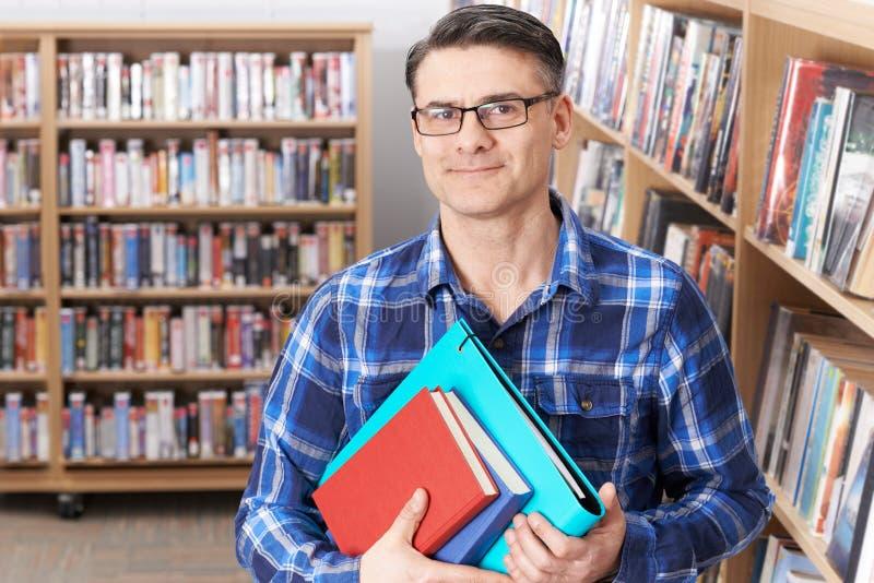 Stående AV den mogna manliga studenten Studying In Library royaltyfri bild