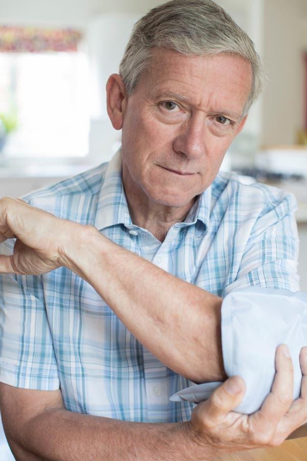 Stående av den mogna mannen som sätter ispacken på smärtsam armbåge royaltyfri bild
