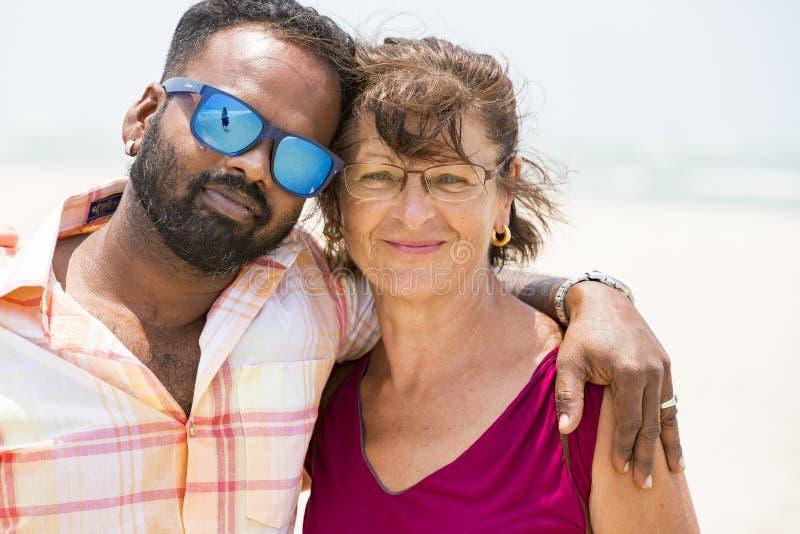 Stående av den multietniska man- och pensionärkvinnan som utomhus går - lyckliga blandras- par på början av kärlekshistorien - in fotografering för bildbyråer