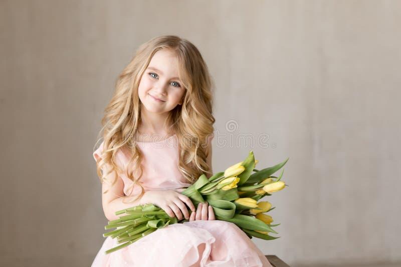 Stående av den mycket härliga unga nätta flickan med gula blommatulpan som ler Inomhus foto härlig tulpan för makrofjädertema När arkivbild
