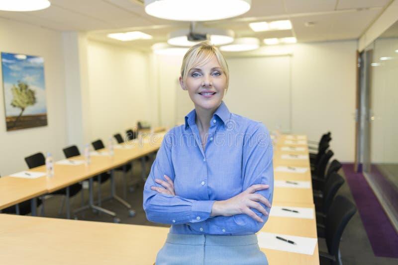 Stående av den nätta affärskvinnan i mötesrum fotografering för bildbyråer