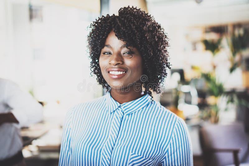 Stående av den nätta afrikansk amerikanaffärskvinnan med afroen som ser och ler på kameran Inre på bakgrund in fotografering för bildbyråer