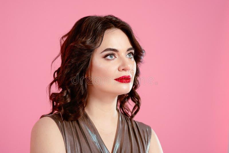 Stående av den nätta attraktiva unga kvinnan för brunett i silverdiskooveraller royaltyfri fotografi