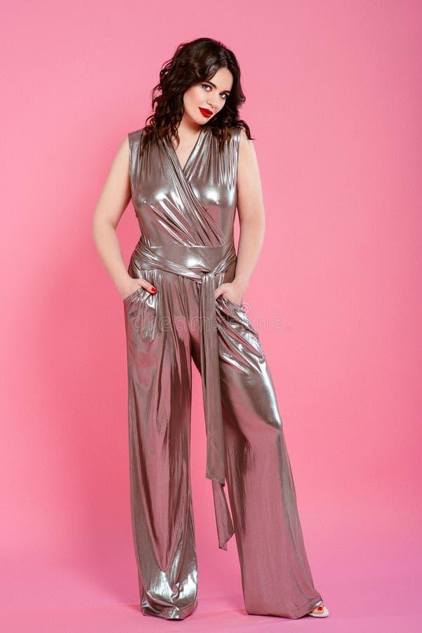 Stående av den nätta attraktiva unga kvinnan för dansbrunett i silverdiskooveraller arkivfoton