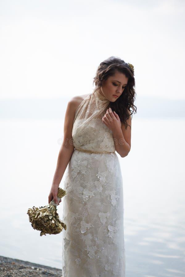 Stående av den nätta bruden i den vita bröllopsklänningen arkivbilder