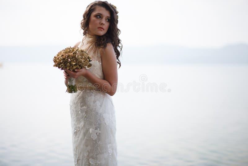 Stående av den nätta bruden i den vita bröllopsklänningen arkivbild
