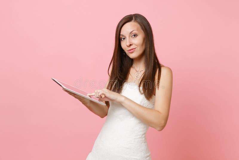 Stående av den nätta brudkvinnan i vitt bröllopsklänningarbete på minnestavlaPCdatoren på pastellfärgad rosa bakgrund royaltyfria foton