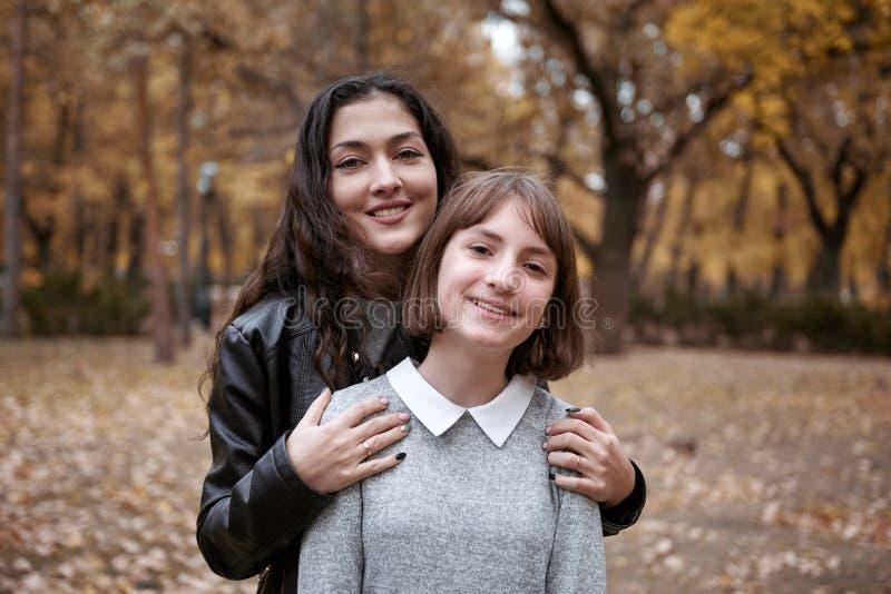 Stående av den nätta kvinnan och den tonåriga flickan De poserar i höst parkerar Härligt landskap på nedgångsäsongen arkivfoton
