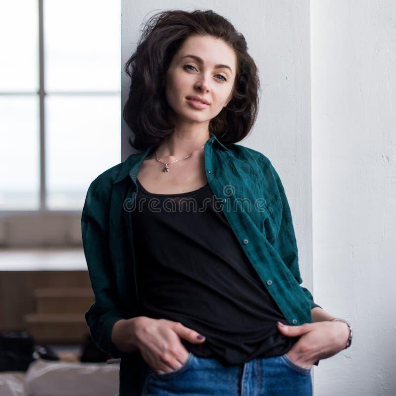 Stående av den nätta le unga kvinnan som bär stilfull tonårig kläder i storformat som står på väggen med hennes hand i jeans royaltyfri bild