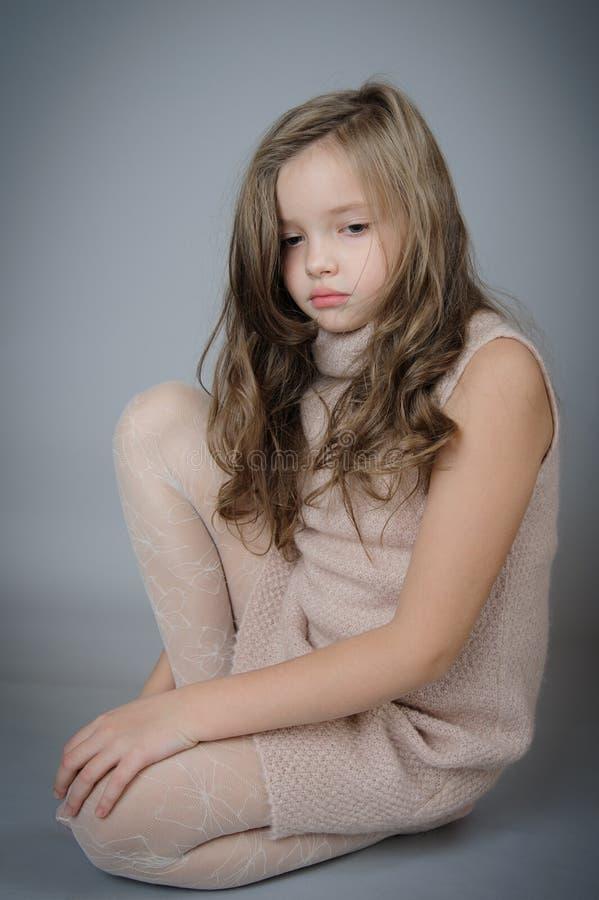 Stående av den nätta ledsna flickan som sitter på golvet arkivbilder