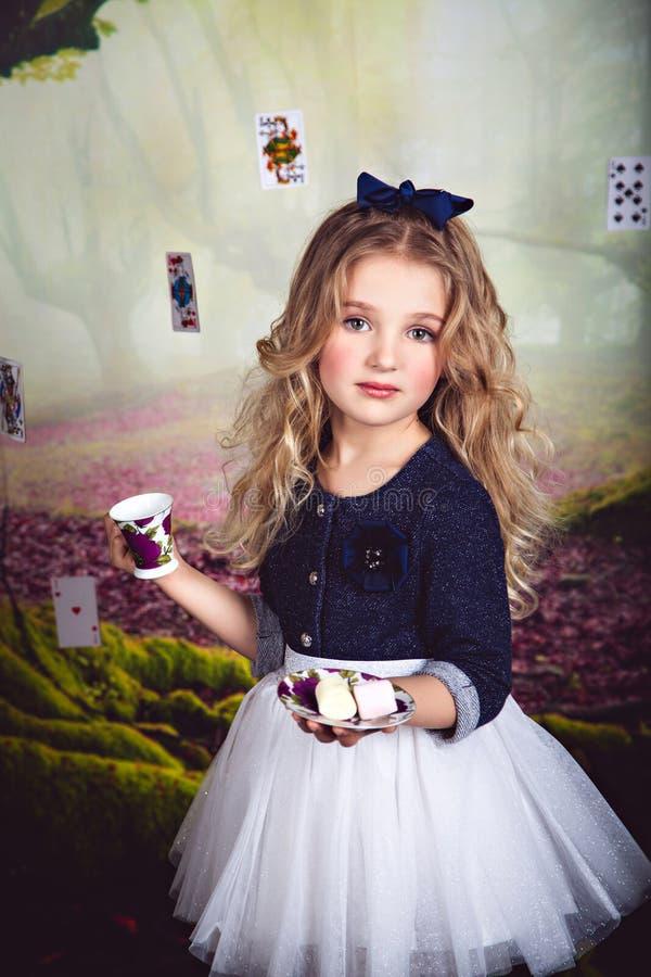Stående av den nätta lilla flickan som Alice i underland arkivbild