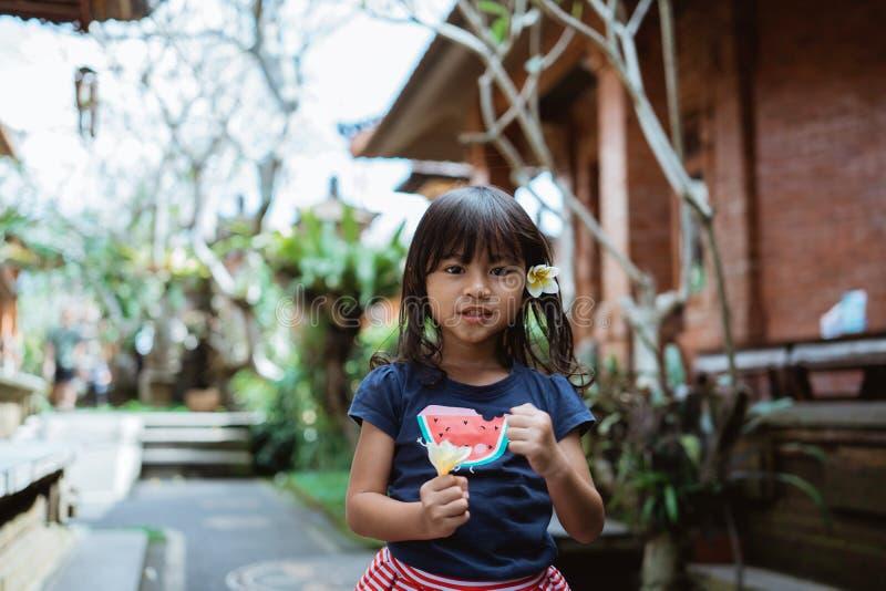 Stående av den nätta lilla flickan som rymmer en frangipaniblomma royaltyfri foto