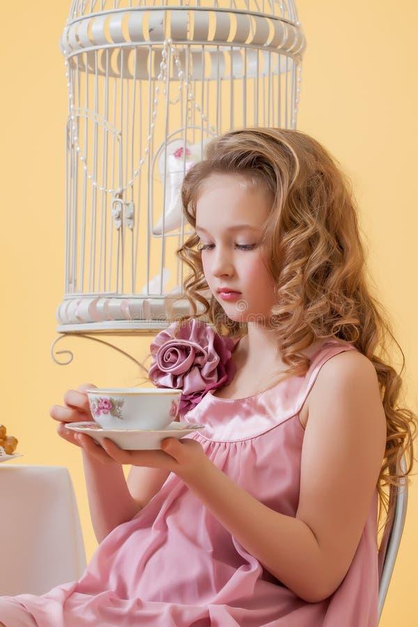 Stående av den nätta lockiga flickan som dricker te arkivbild