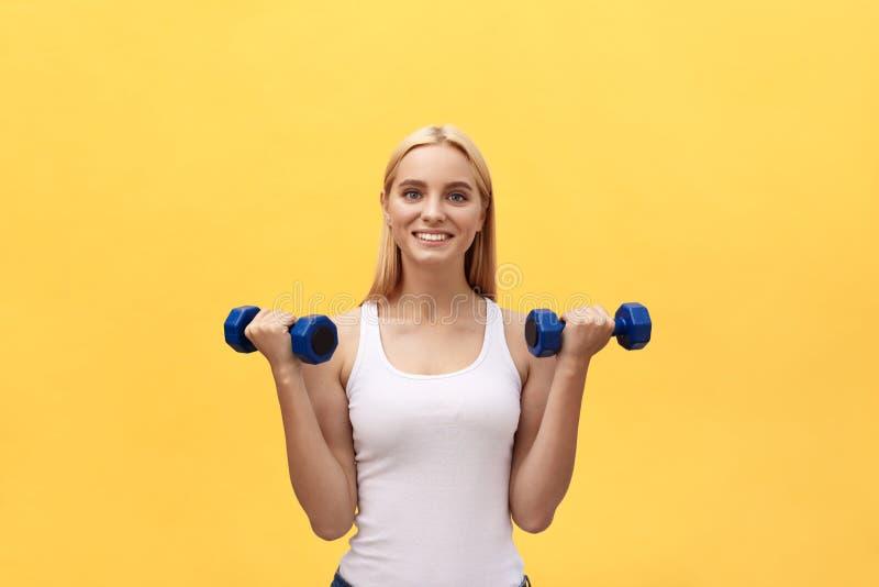 Stående av den nätta sportiga flickan som rymmer vikter och att le Isolerat över gul bakgrund royaltyfri foto