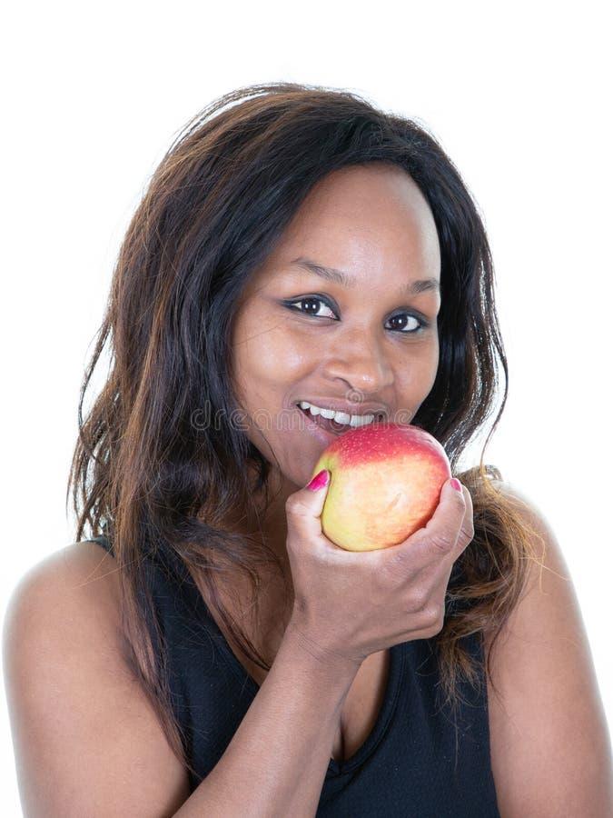 Stående av den nätta svarta kvinnan som äter ta tuggan av det röda äpplet arkivbilder