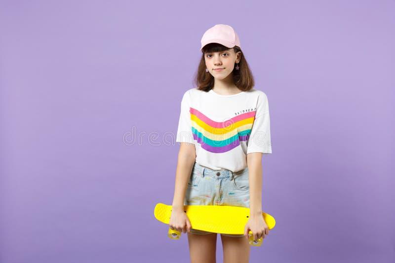 St?ende av den n?tta ton?riga flickan i livlig kl?der som ser kameran som rymmer den gula skateboarden isolerad p? violett pastel royaltyfri foto