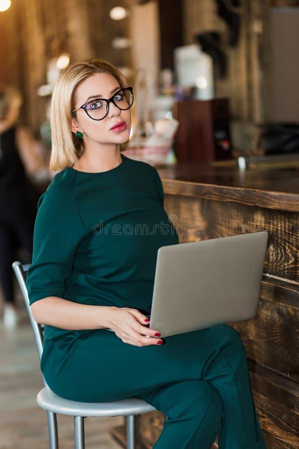 Stående av den nätta unga affärskvinnan i exponeringsglas som sitter på arbetsplats arkivbild