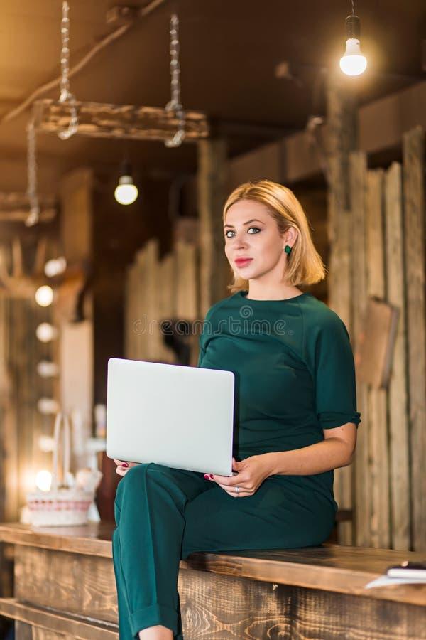 Stående av den nätta unga affärskvinnan i exponeringsglas som sitter på arbetsplats royaltyfri foto