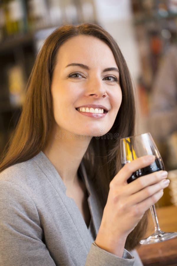 Stående av den nätta unga kvinnan som dricker rött vin i restaurang royaltyfri fotografi