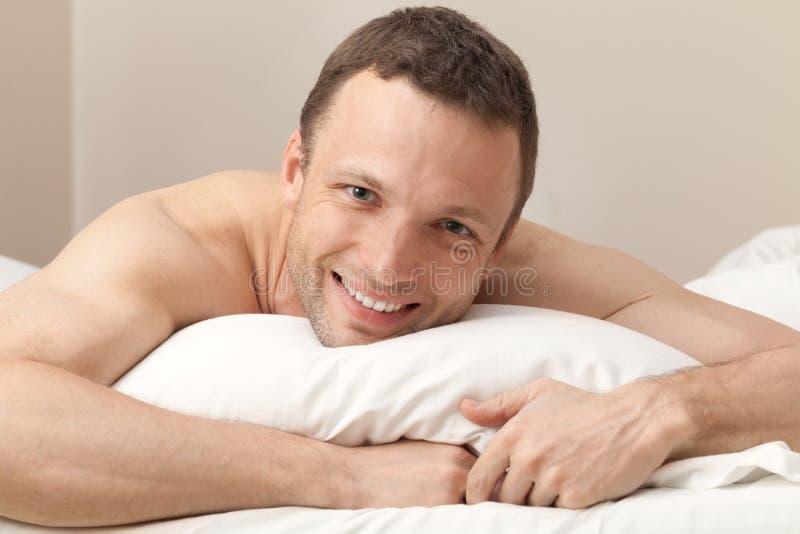 Stående av den nöjda unga mannen i säng royaltyfria bilder