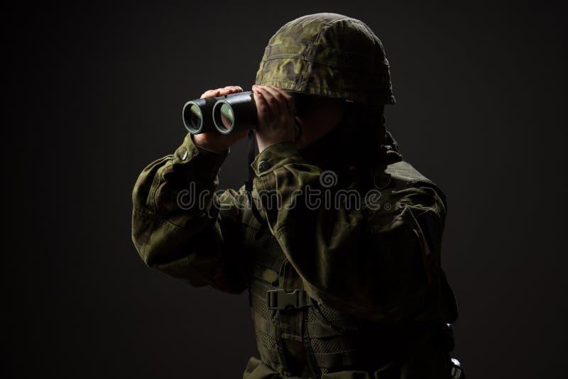 Stående av den obeväpnade kvinnan med kamouflage Den unga kvinnliga soldaten observerar med kikare arkivfoto