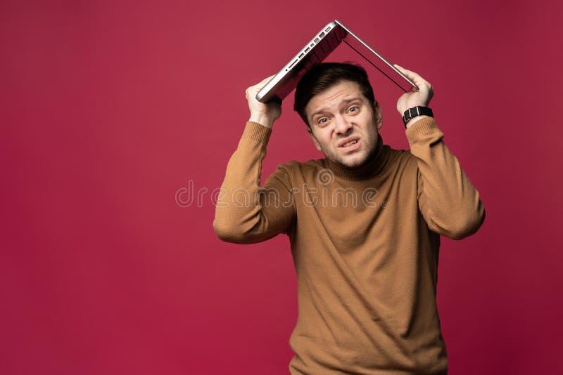 Stående av den olyckliga stressade unga skäggiga maninnehavbärbara datorn ovanför huvudet, medan stsanding som isoleras över rosa arkivfoton